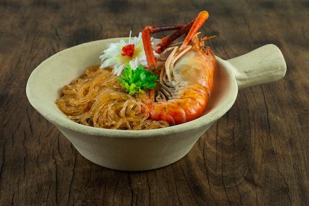 냄비 버미첼리에 유리 국수를 곁들인 구운 새우 중국 음식 아시아 스타일은 코레인더 태국 야채와 조각된 부추 뭉치 양파 측면을 장식합니다.