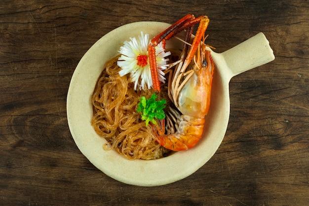 냄비 버미첼리에 유리 국수를 곁들인 구운 새우 중국 음식 아시아 스타일은 코레인더 태국 야채와 조각된 부추 뭉치 양파 탑뷰를 장식합니다.