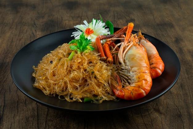 블랙 플레이트에 유리 국수 버미첼리를 곁들인 구운 새우 중국 음식 아시아 스타일은 코레인더 태국 야채와 조각된 부추 뭉치 양파 측면을 장식합니다.