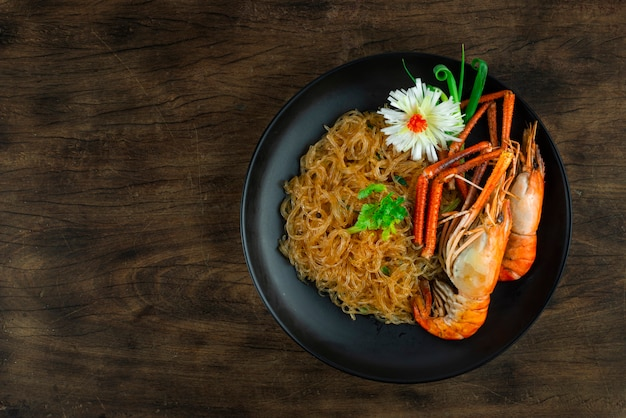 블랙 플레이트에 유리 국수 베르미첼리를 곁들인 구운 새우 중국 음식 아시아 스타일은 코레인더 태국 야채와 조각된 부추 뭉치 양파 탑뷰를 장식합니다.