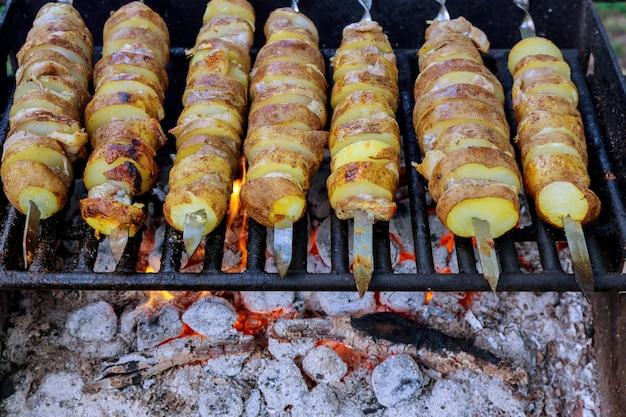 Запеченный нарезанный картофель на шпажках на гриле с огнем.
