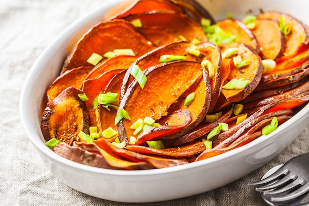Baked sliced sweet potato with green onions in white dish.