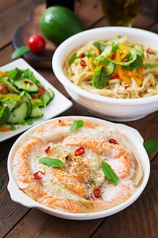 Baked slices of red and white fish with honey and lime juice, served with fresh salad and soft noodles in miso broth