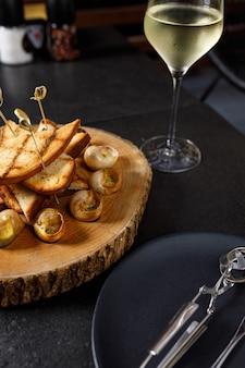 나무 판자에 마늘 기름과 허브를 넣은 구운 달팽이