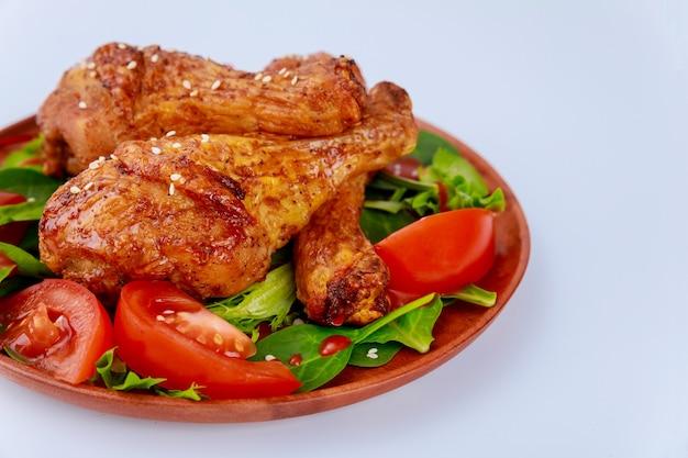 흰색 표면에 샐러드와 구운 된 매운 치킨 드럼 스틱. 확대.