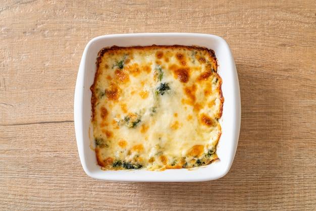 흰 접시에 치즈와 함께 구운 시금치 라자냐