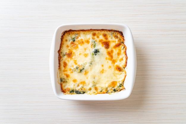 Запеченная шпинатная лазанья с сыром в белой тарелке