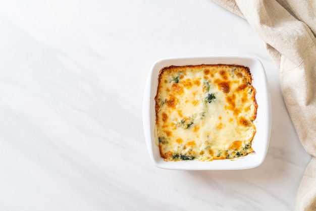Baked spinach lasagna with cheese in white plate