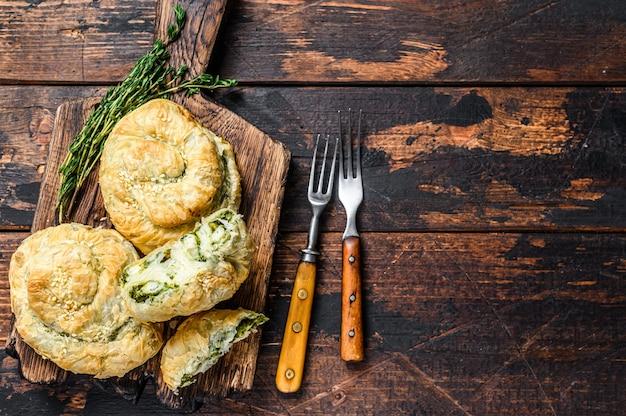페타 치즈와 시금치를 곁들인 구운 나선형 필로 페이스트리 퍼프. 어두운 나무 테이블. 평면도.