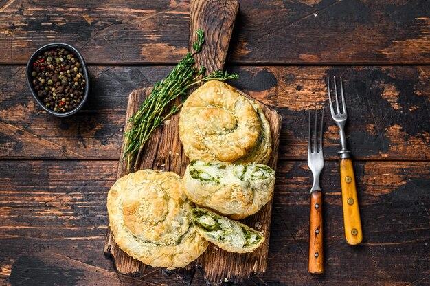 페타 치즈와 시금치를 곁들인 구운 나선형 필로 페이스트리 퍼프.