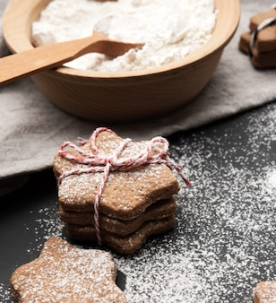 Baked star-shaped gingerbread cookie sprinkled with powdered sugar on a black table and ingredients, close up