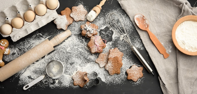 Baked star-shaped gingerbread cookie sprinkled with powdered sugar on a black table and ingredients, top view