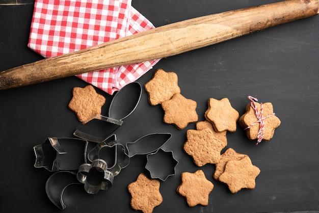 Запеченные имбирные пряники в форме звезды, деревянная скалка и металлические резаки на черном столе, вид сверху