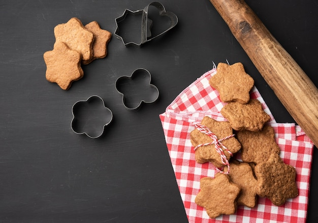 Baked star shaped gingerbread cookies, wooden rolling pin and metal cutters on a black table, top view