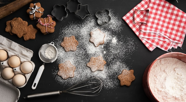 Запеченное имбирное печенье в форме звезды, посыпанное сахарной пудрой, на черном столе и ингредиенты