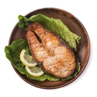 레몬과 흰색 표면에 샐러드와 구운 된 스테이크 송어