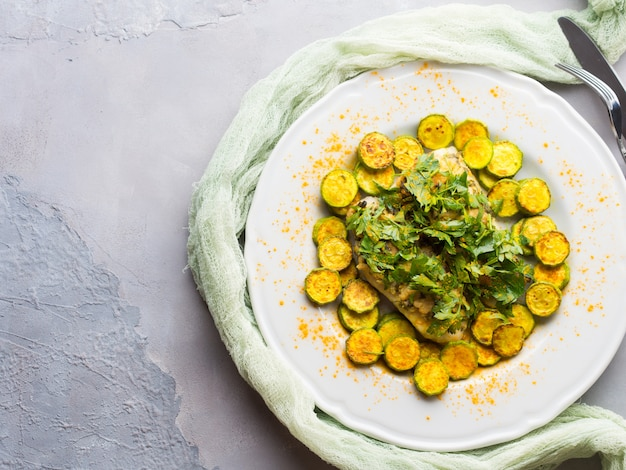 Baked stock fish fillet with almond parsley topping and turmeric courgettes on white plate. healthy diet dish