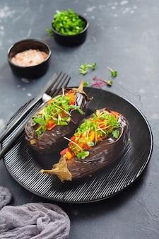 Запеченные фаршированные баклажаны с разными овощами, помидорами, перцем, луком и петрушкой в круглой черной тарелке на темном каменном или бетонном столе. вид сверху.