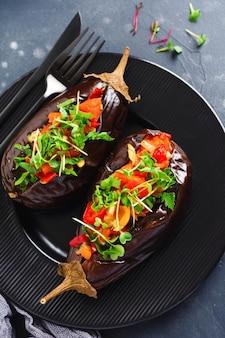 검은 돌이나 콘크리트 테이블 배경에 다양한 야채, 토마토, 후추, 양파, 파슬리를 넣은 구운 가지. 평면도