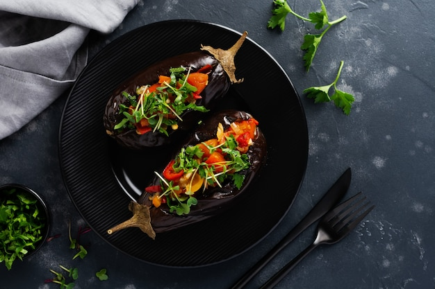 검은 돌 또는 콘크리트 테이블에 다른 야채, 토마토, 후추, 양파 및 파슬리로 구운 박제 가지