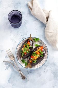 회색 돌이나 콘크리트 테이블 배경에 다양한 야채, 토마토, 후추, 양파, 파슬리를 넣은 구운 가지. 평면도