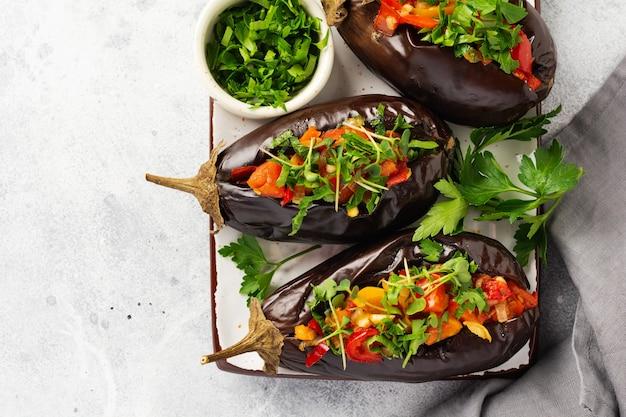 회색 돌 또는 콘크리트 테이블에 다른 야채, 토마토, 후추, 양파 및 파슬리로 구운 박제 가지