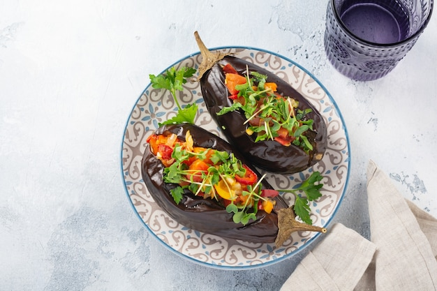 회색 돌 또는 콘크리트 테이블 테이블에 다른 야채, 토마토, 후추, 양파, 마이크로 그린 및 파슬리로 구운 박제 가지. 평면도.