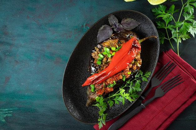 Baked stuffed eggplant with minced meat and hot chili on a black plate top view.