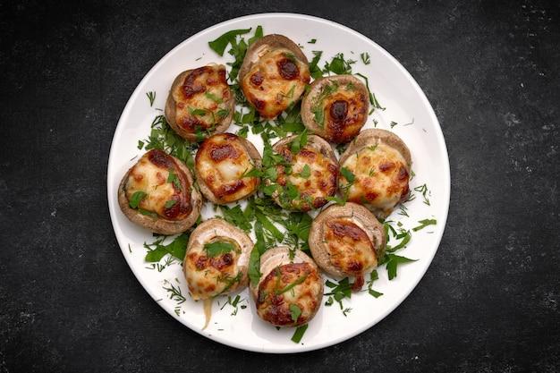 Запеченные фаршированные грибами шампиньоны, с сыром и зеленью, на белой тарелке, на черном фоне