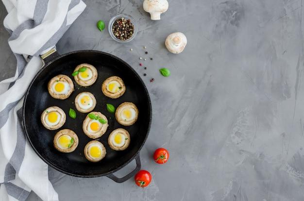 暗いコンクリートの背景に古い鋳鉄製のフライパンでタイムの葉とウズラの卵と焼きキノコを詰めた。