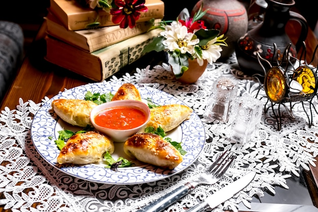 Baked stuffed pastry with sesame sprinkles served with tomato sauce