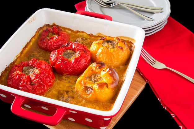 Baked stuffed peppers with minced meat, rice, in sauce on the black background.