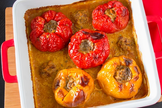 Baked stuffed peppers with minced meat, rice, in sauce