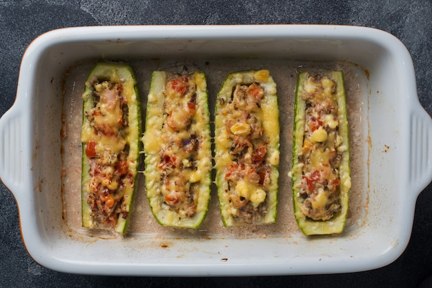 Baked stuffed zucchini boats with minced chicken mushrooms and vegetables with cheese on a baking sheet. top view copyspace