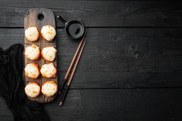 焼き寿司巻き寿司、サーモン、カニ、キュウリ、アボカド、フライングフィッシュロー、スパイシーソースセット、黒い木製のテーブル