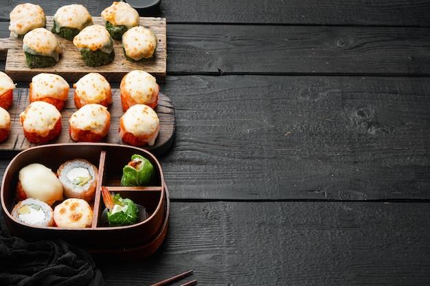 Запеченные суши-маки роллы с лососем, крабом, огурцом, авокадо, икрой летучей рыбы на черном деревянном столе