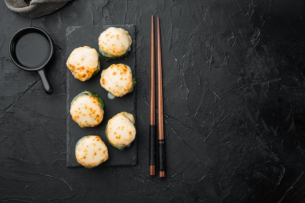 Запеченный суши-ролл с креветками и шляпкой из икры масаго. набор блюд традиционного суши-ресторана на черном камне