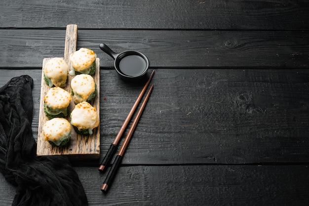 Запеченный суши-ролл с креветками и шляпкой из икры масаго. набор блюд традиционного суши-ресторана, на черном деревянном столе
