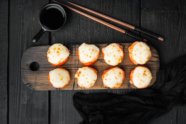 エビとマサゴのキャビアキャップが付いた焼き寿司ロール。黒い木製のテーブルの上に、伝統的な寿司レストランの料理セット