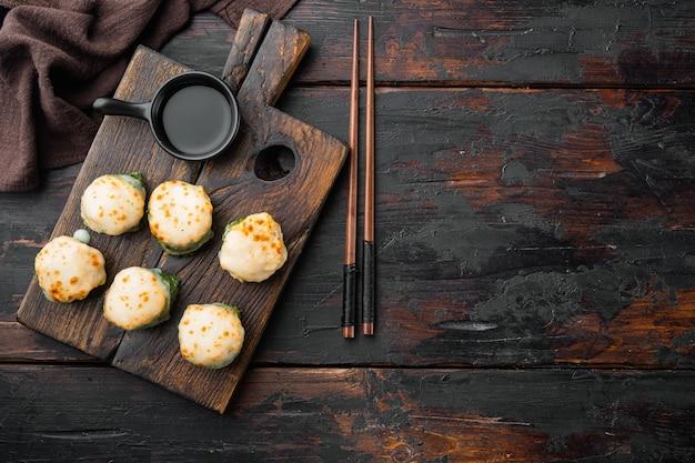 エビとマサゴのキャビアキャップが付いた焼き寿司ロール。古い暗い木製のテーブルの上に、伝統的な寿司レストランの料理セット