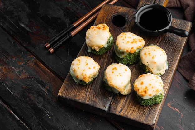 Запеченный суши-ролл с креветками и шляпкой из икры масаго. набор блюд традиционного суши-ресторана на старом темном деревянном столе
