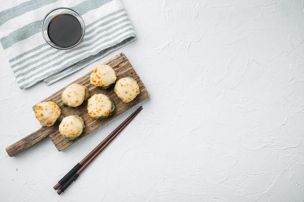 Запеченный суши-ролл с креветками и шляпкой из икры масаго. набор блюд традиционного суши-ресторана, на белом камне