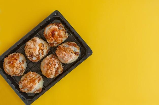 노란색 배경에 플라스틱 포장에 연어를 넣은 구운 스시 - 플라스틱 상자에 있는 밝고 맛있는 스시 롤