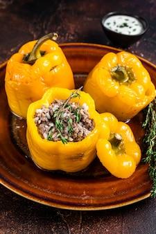 Запеченный сладкий болгарский перец, фаршированный говядиной, рисом и овощами. темный фон. вид сверху.