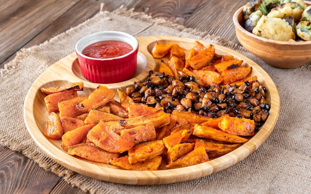 Baked sweet potato with fried mushrooms on the wooden tray