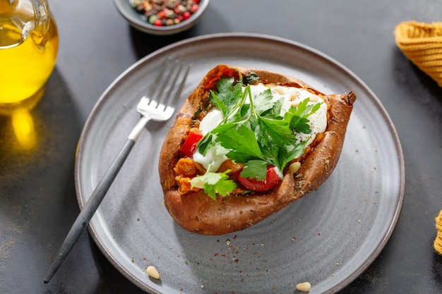 Baked sweet potato with sour cream and beans with parsley served on plate. closeup.
