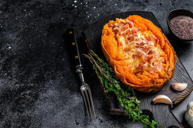 Запеченный батат из сладкого картофеля, фаршированный говяжьим фаршем и сыром. черный фон. вид сверху. скопируйте пространство.