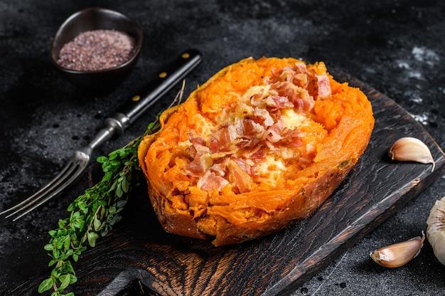 Запеченный батат из сладкого картофеля, фаршированный говяжьим фаршем и сыром. черный фон. вид сверху.