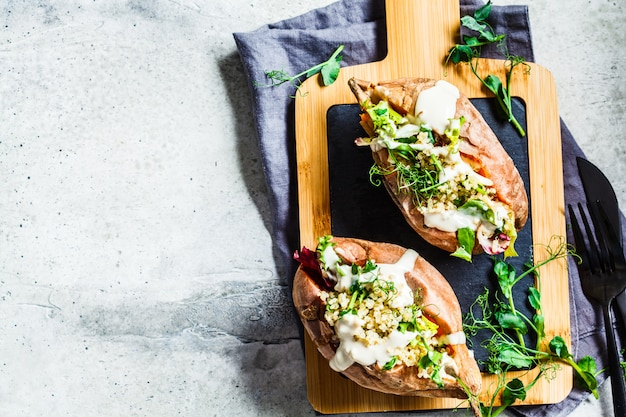 Baked sweet potatoes stuffed with quinoa, vegetables and tahini