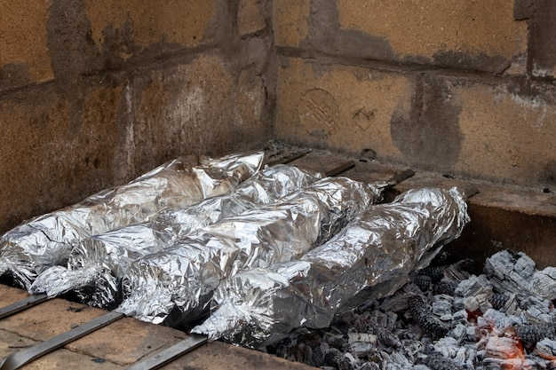 Baked sweet potatoes wrapped with aluminum foil roasting.burned by heat on the fireplace, with bamboo, with a tongs placed on the stove, a useful food and warming the body at street food thailand.